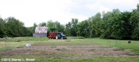 Tractor in unmowed field behind East Garden